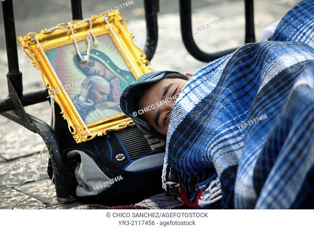 A pilgrim sleeps close to an image of the Virgin of Guadalupe and Pope John Paul II at the pilgrimage to Our Lady of Guadalupe Basilica in Mexico City, Mexico