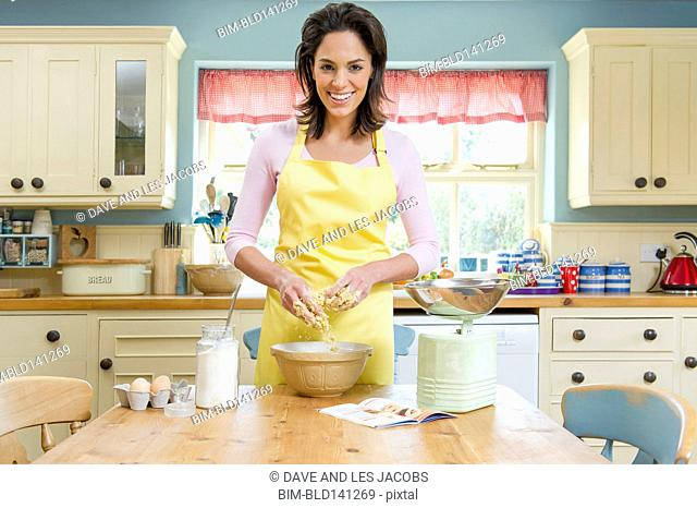 Hispanic woman baking at kitchen table