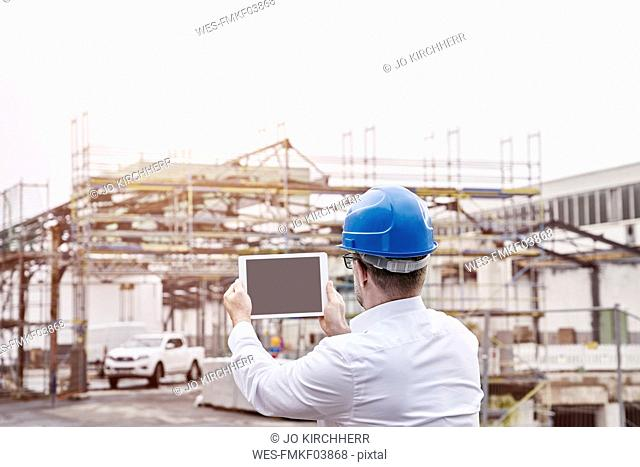 Back view of man wearing blue hart hat taking picture with tablet at construction site