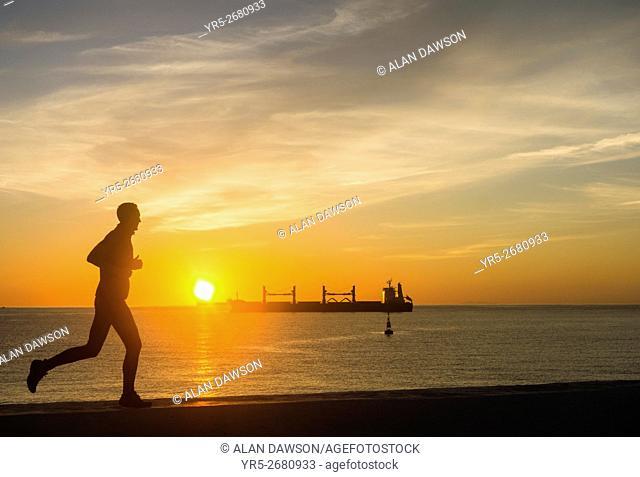 A jogger on sea wall as the sun rises over the Atlantic Ocean from Avenida Maritima in Las Palmas, Gran Canaria, Canary Islands, Spain,