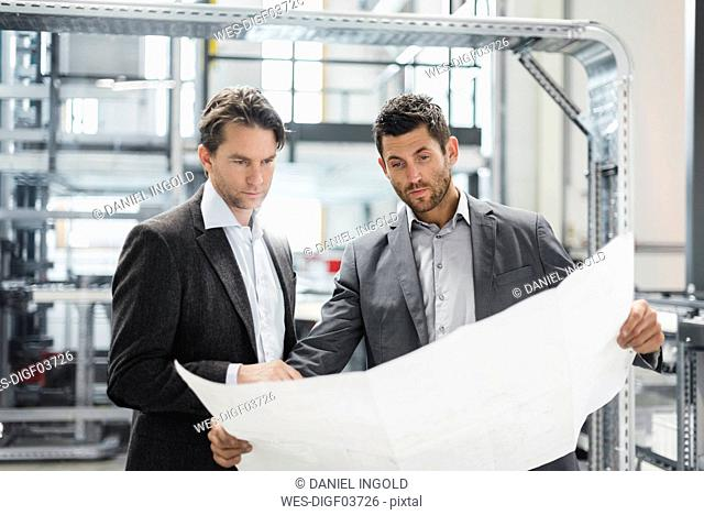 Two businessmen looking at plan in modern factory