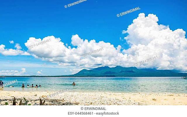 An empty beach with golden sand and blue skies