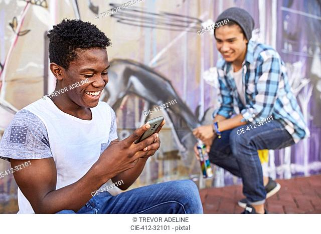 Smiling teenage boys hanging out texting and spray painting graffiti on urban wall