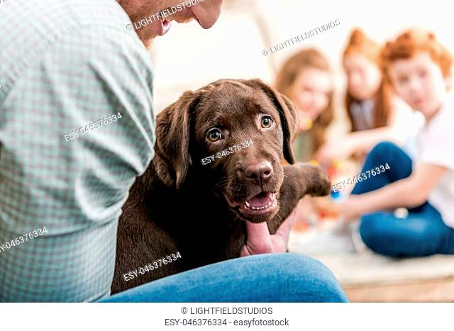 father holding labrador retriever puppy, happy family behind at home, family fun at home concept