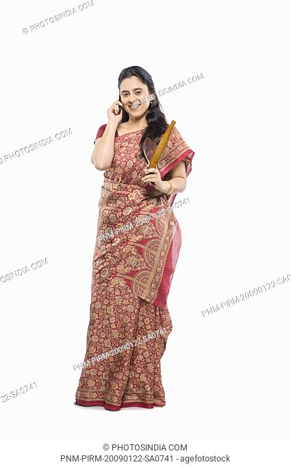 Woman talking on a mobile phone and holding a rolling pin