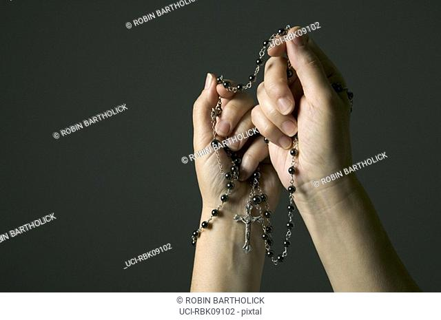 Woman praying with rosary beads