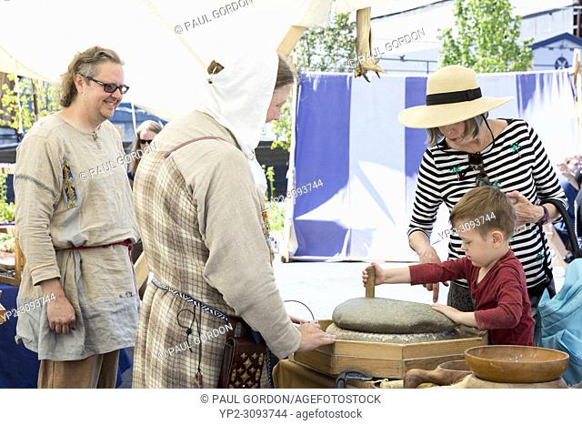 Seattle, Washington: James (left) and Jurunn, in period dress, demonstrate the use of a quern to mill grain in a Viking kitchen at the Nordic Museum's 35th...