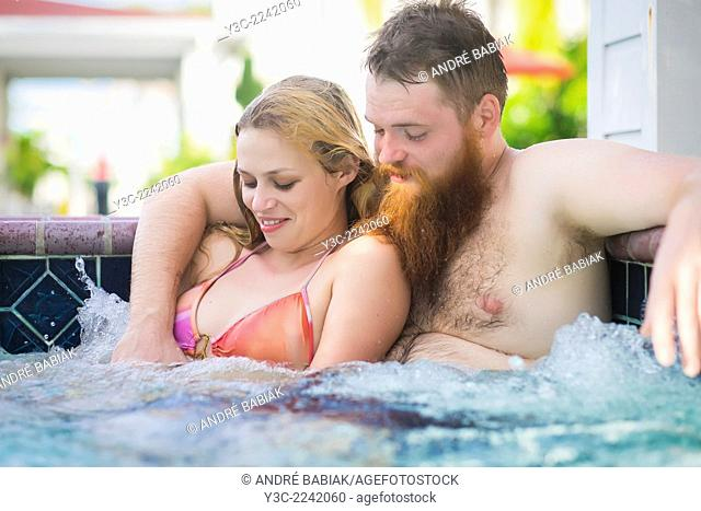 Man and woman in the 20s taking a bath in a hot tub wellness area