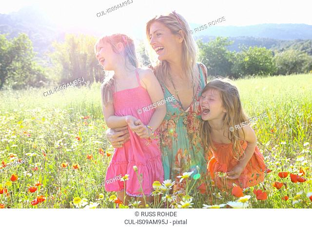 Mid adult woman and two daughters laughing in wildflower meadow, Majorca, Spain