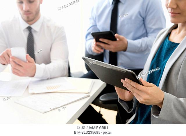 Business people using digital tablets and cell phone in office