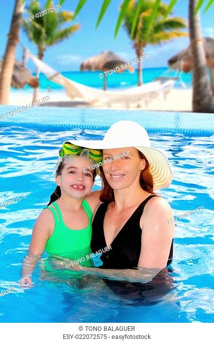 mother and daughter hug in pool tropical beach