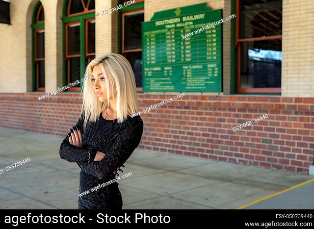 A gorgeous young blonde model poses outdoors while waiting for a train at a train depot