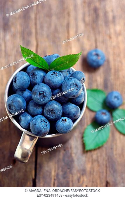 Blueberries in a cup on a wooden table