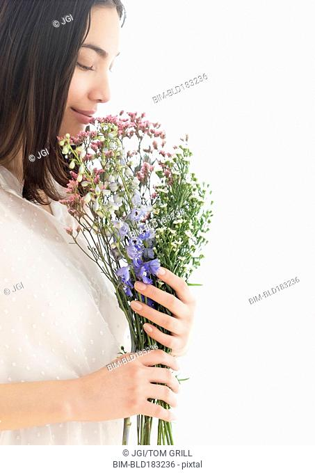 Hispanic woman smelling bouquet of flowers