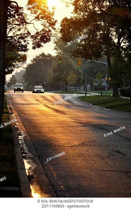 Two cars wait as the traffic light turns green while the eastern sky has a ruddish glow at day break on a gleaming city street in Ontario, Canada