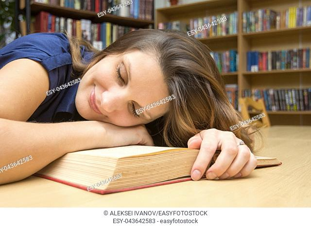 The girl lay down on a book in the library and smiles having closed her eyes