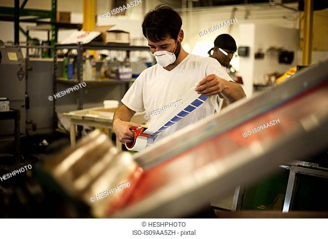 Worker measuring adhesive tape in screen printing workshop