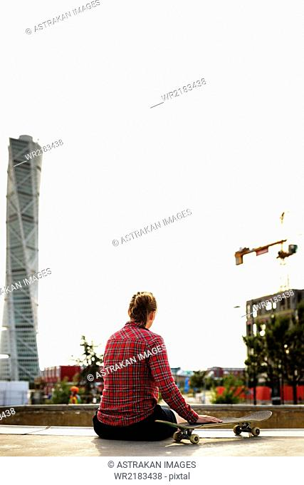 Rear view of young woman relaxing at skateboard park with Turning Torso in background