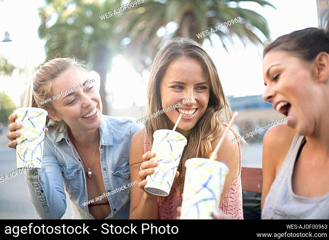 Carefree friends drinking chilled drinks at beach during vacation