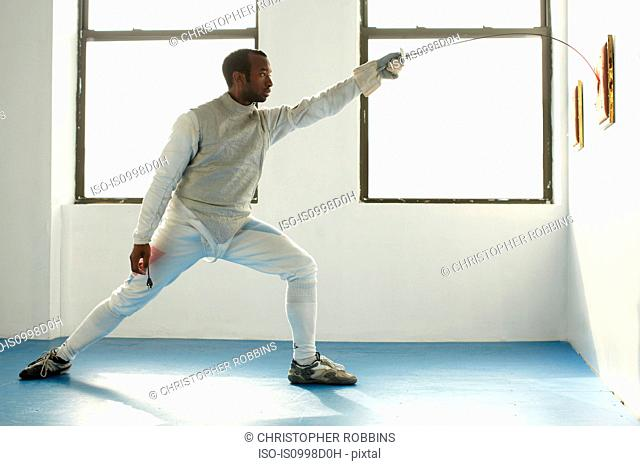 Male fencer holding foil to target, side view