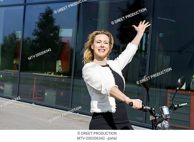 Businesswoman riding electric powered scooter