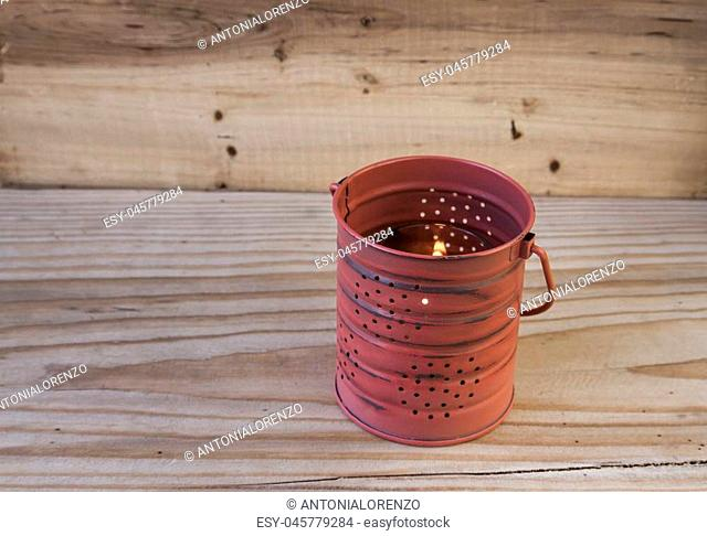 Decorative tin can lantern on a wooden background