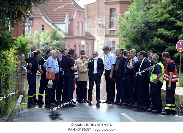 Chancellor Angela Merkel (C LEFT, CDU) and Torsten Albig (C RIGHT, SPD), governor of Schleswig-Holstein stands with helpers in the partly flooded oldtown of...