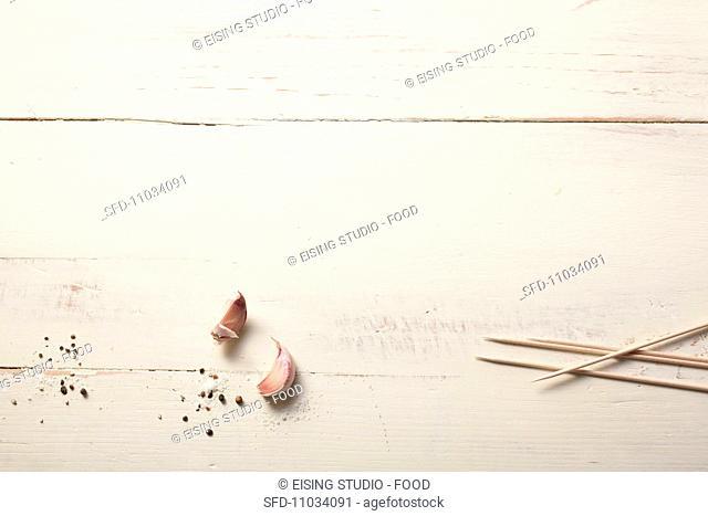 Garlic cloves, salt, pepper and kebab sticks on a wooden surface