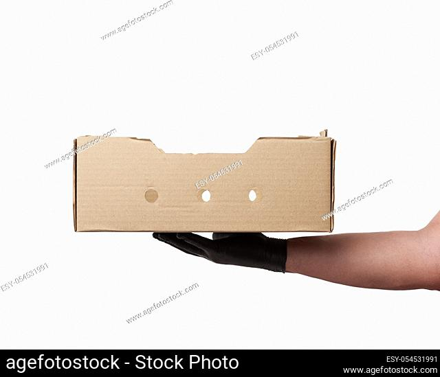 male hand in a black latex glove holds an empty brown cardboard box on a white background, safe and contactless delivery of on-line orders during epidemics