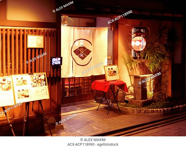 Mitoko, traditional Japanese Kaiseki restaurant lit by the lights of lanterns at night with a Noren curtain in the entrance door and menus displayed outside