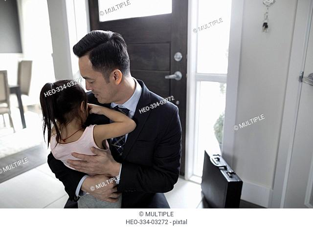 Daughter greeting and hugging businessman father at front door