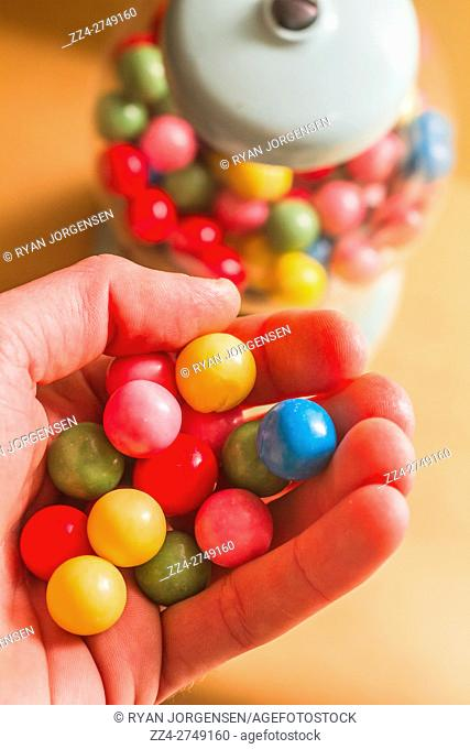 Handfull of colorful gumballs near candy dispenser from first person perspective view