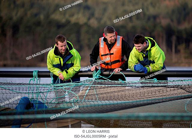 Workers on salmon farm in rural lake
