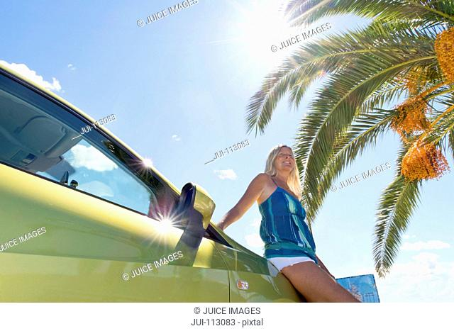 Smiling woman leaning on car under palm tree and sun in blue sky