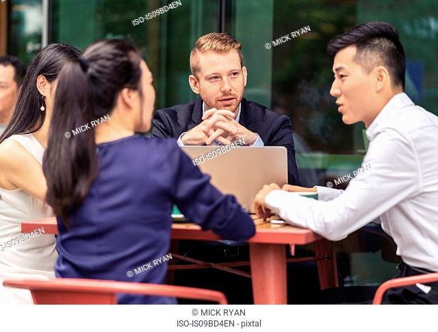 Group of businesspeople, having meeting at cafe, using laptop, outdoors