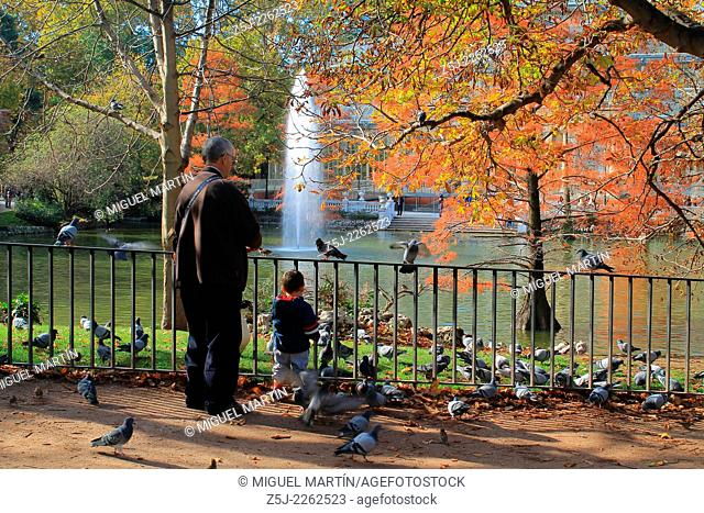 An elder man and his grandson play with pigeons and gooses beside the pond of Palacio de Cristal in Madrid's Retiro Park