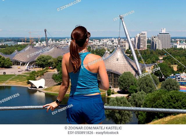 Female jogger relaxing after working-out listening to music enjoying the view over Munich olympic park