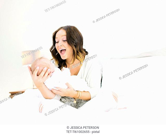 Mother sitting on bed carrying daughter (0-1 months) and laughing