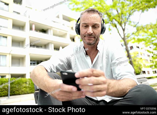 best ager man checking smartphone in residential area