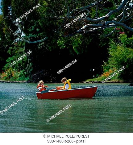 Two children sitting in a boat