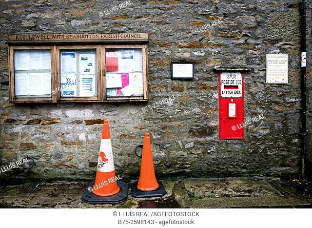 Kettlewell with Starbotton board Parish Council, Post Office Letter Box, and two traffic cones in a facade of a house. Kettlewell, Skipton, North Yorkshire