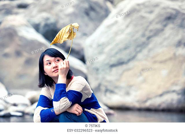 Young asian woman sitting near a pond at a stone desert with a large yellow leaf in her hand