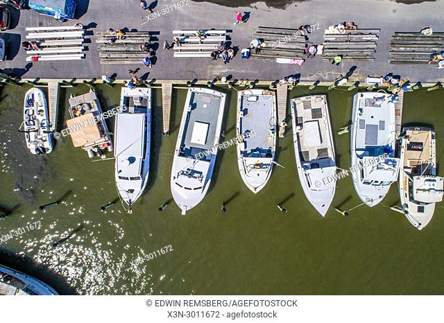 Shot from directly above of a group of motor boats sitting idle at dock with people sitting in grand stands, Deal Island, Maryland. USA