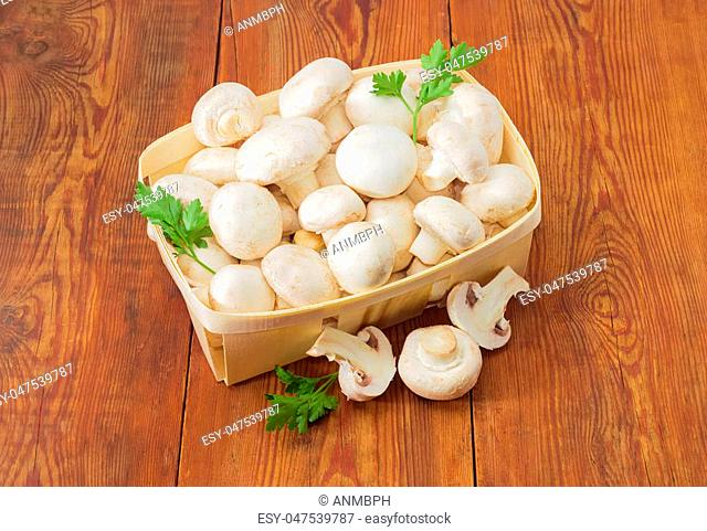 Fresh cultivated button mushrooms and twigs of parsley in the wooden basket, one whole mushroom and mushroom cut in half separately beside on an old wooden...