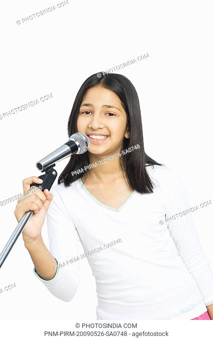 Portrait of a girl singing into a microphone
