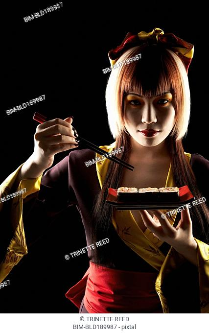 Asian woman in traditional clothing eating sushi
