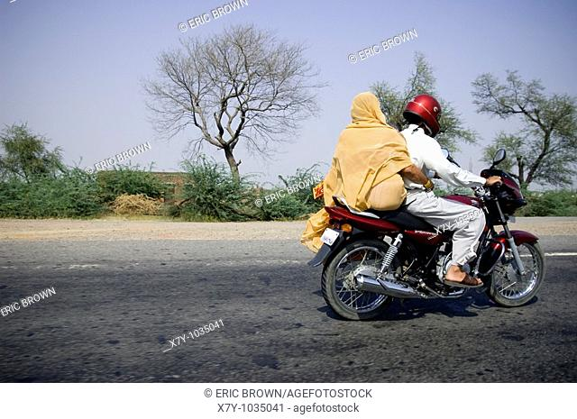 A couple rides on a freeway on a motorcycle in India