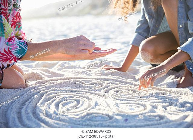 Mother and daughter placing seashells in spirals in sand on sunny summer beach