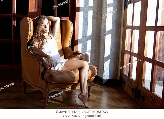 sexy girl sitting on a chair looking through the window