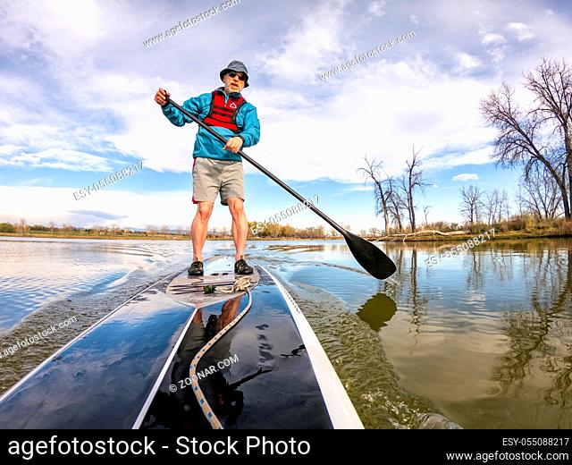 athletic senior man on a stand up paddleboard on a calm lake in Colorado, bow view
